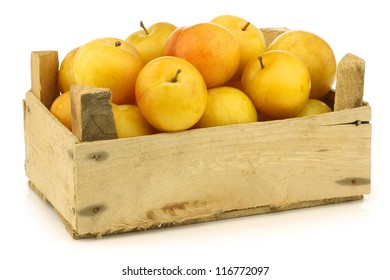 fresh yellow plums in a wooden crate on a white background