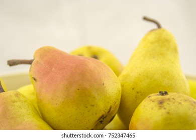Fresh, yellow, red, juicy pear on a wooden base and white background color