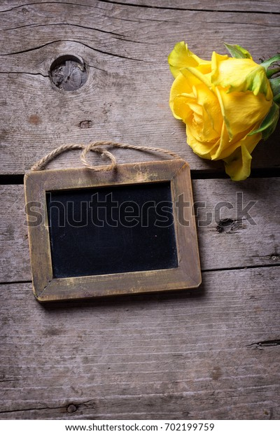 Fresh yellow rose flower and empty little blackboard  on  rustic wooden  background. Selective focus is on tag. Place for text.