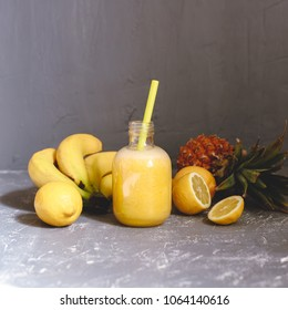 Fresh yellow smoothie with lemons, banana and pineapple on gray background.