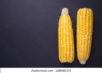 Fresh yellow sweet corn on the cob. Studio shot on black stone board background. For food concept. Top view
