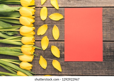 Fresh, yellow tulips arranged on the left of the frame. In the middle there is a card with the possibility to save the text. Flowers lie on natural boards creating a perfect frame with free space.