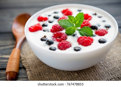 fresh yoghurt with raspberry and green mint on wooden table. sweet dessert food