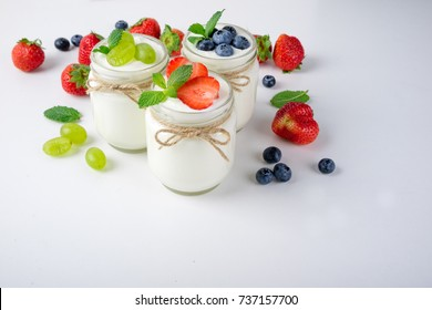 Fresh yogurt with berries in glass jars. Dairy products. Healthy food, dieting and breakfast concept. Copy space