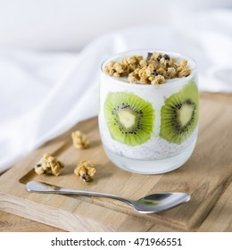 Fresh yogurt with kiwi on the wooden table with spoon