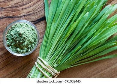 Fresh young barley grass with green barley grass powder on a wooden background