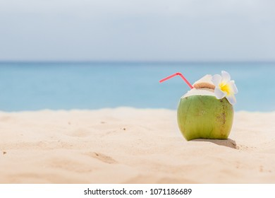 Fresh young coconut lying on the sand beach background with straw ready for drink. Tropical vacation travel concept