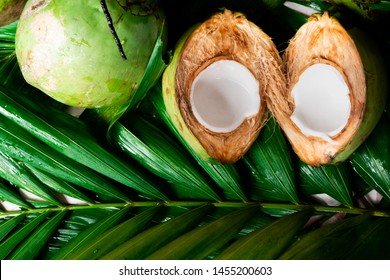 Fresh young coconut split in half showing white flesh with pile of coconuts
