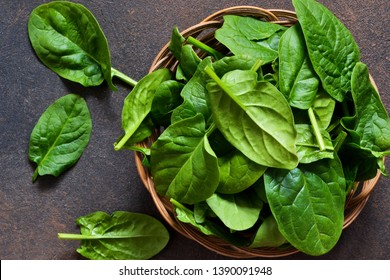 Fresh, young green spinach on a concrete background. View from above.