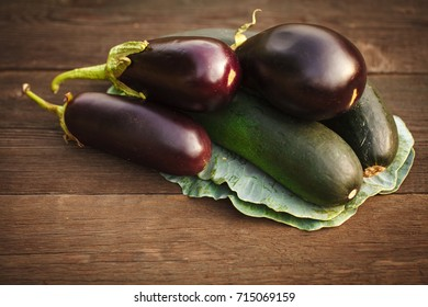 Fresh zucchini and eggplant on a wooden table. Background