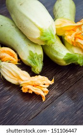 Fresh zucchini with leaves and flowers on a wooden board