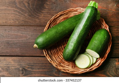 Fresh zucchini on wicker mat on wooden background