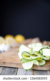 Fresh zucchini sliced into ribbons and sitting on wooden cutting board with copy space at top.