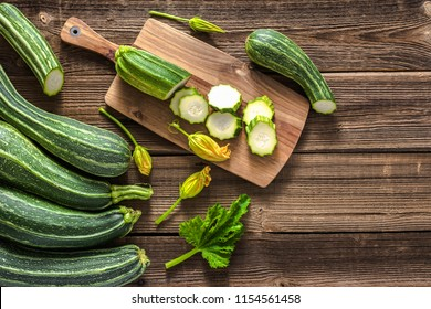 Fresh zucchini and slices of zucchinis on wooden table. Sliced courgette, healthy vegan diet or vegetarian food, cooking concept.
