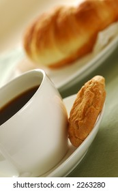 Fresh-baked croissant, cookies and cup of coffee. Shallow DOF. Focus on cup and cookies.
