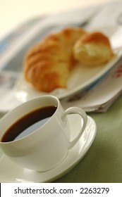 Fresh-baked croissant, cup of coffee and newspaper. Shallow DOF. Focus on cup.