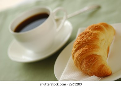 Fresh-baked croissant and cup of coffee. Shallow DOF. Focus on croissant.