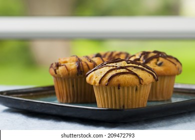 Freshly backed chocolate banana muffins cooling on a table near a window.