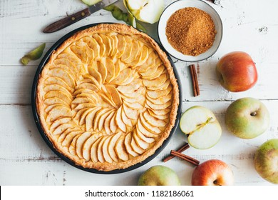 Freshly baked apple pie tart with custard filling on a rustic white wooden background. Top view
