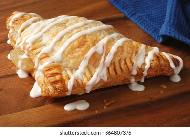 Freshly baked apple turnover with drizzled icing on wooden serving tray. Closeup with shallow dof.