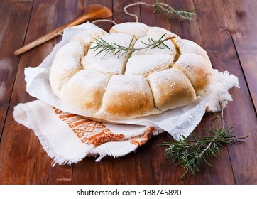 Freshly baked Australian damper loaf with rosemary on a rustic cloth on wooden background