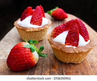 Freshly baked baskets with curd cream and strawberries