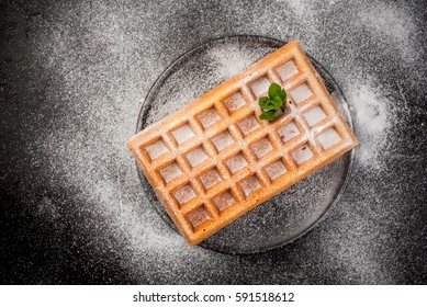Freshly baked Belgian waffles, sprinkled with powdered sugar. On a black plate on a black stone table. Top view, copy space