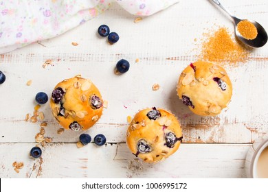 Freshly baked blueberry muffins with almond, oats and icing sugar topping on a rustic white wooden table and a mug of coffee with a spoon of brown sugar. Top view.