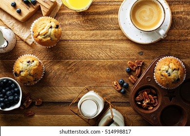 Freshly baked blueberry muffins in a rustic setting with milk and coffee on the table overhead shot with copyspace