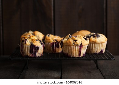 Freshly baked blueberry muffins served on cooling rack on dark wooden table. Moody lighting, rustic and natural atmosphere.