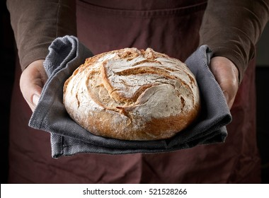 freshly baked bread in bakers hands