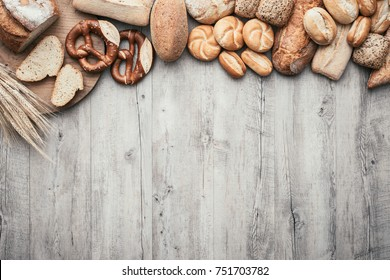 Freshly baked bread, chopping board and ears of wheat on a wooden worktop, bakery and healthy eating flat lay banner