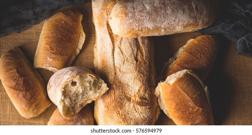 Freshly baked bread loaves on burlap dark wooden background. Texture closeup italian bakery products. Top view