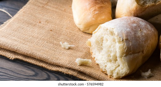 Freshly baked bread loaves on burlap dark wooden background. Texture closeup italian bakery products