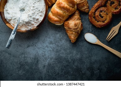 Freshly baked bread on wooden table,Bakery Concept- gold rustic crusty loaves of bread and buns on black chalkboard background. captured from above (top view, flat lay. Layout with copy space.
