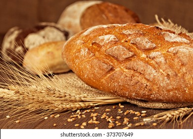 Freshly baked breads with grains and ears . Shallow depth of field.