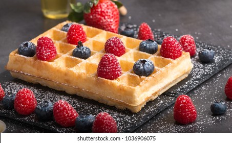 Freshly baked Brussels waffles on a black stone plate with fresh strawberrys and blueberrys and raspberrys on a dark stone table with honey and coffee.