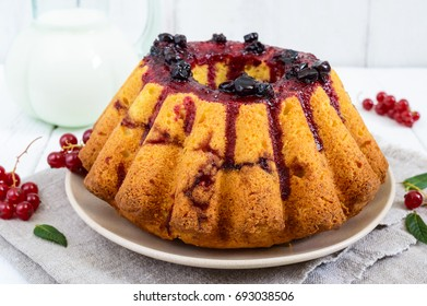 Freshly baked cake with summer berries, jug of milk on a white background