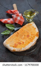 Freshly baked calzone pizza over grey cracked stone background, vertical shot, selective focus
