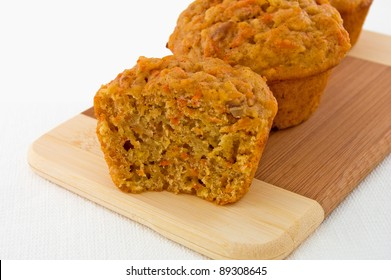 Freshly baked carrot muffins on a wooden cutting board.