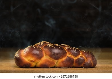 Freshly baked challah from the oven on a wooden table. Steam rises above the bread. Close-up, festive bread