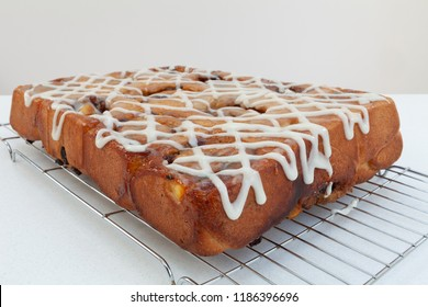 Freshly baked chelsea buns cooling on a wire rack.  The buns are sugar glazed and iced with white icing sugar. Viewed from an angle.
