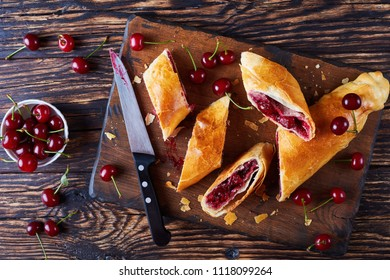 freshly baked cherry strudel on a rustic wooden cutting board with knife and fresh cherries at the background, classic recipe, view from above, flat lay