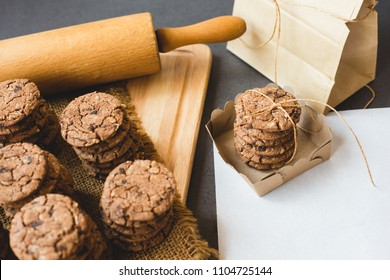 Freshly baked chocolate chip cookies with packaging and rolling pin on tray