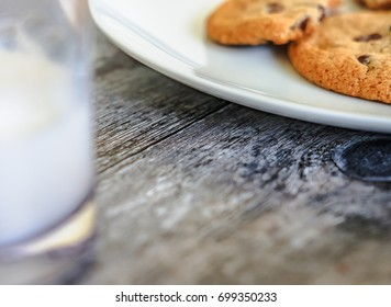 Freshly baked chocolate chip cookies seen on a food plate together with an out of focus, partially drunk glass of cold milk in the foreground. Shown on a kitchen, wooden work surface.
