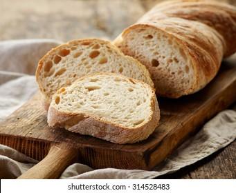 freshly baked ciabatta bread on wooden cutting board