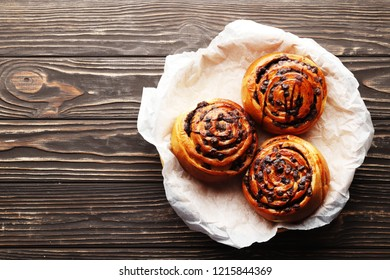 Freshly baked cinnamon buns with spices and cocoa filling on parchment paper. Top view. Sweet Homemade Pastry christmas baking. Close-up. Kanelbule - swedish dessert. Copy space.