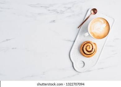 Freshly baked cinnamon roll with spices and cocoa filling and coffee or cappuccino with latte art on white serving plate over white marble background. Top view. Copy space for text. Swedish breakfast.
