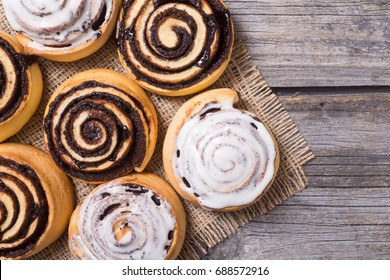 Freshly baked cinnamon rolls buns with cocoa on wooden background . Top view . Space for text