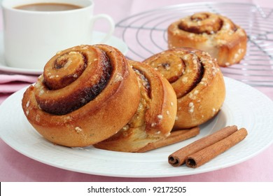 Freshly baked cinnamon rolls with a cup of coffee.